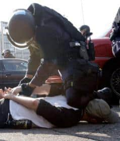 Image of protestor prostrate with police officer kneeling on his neck